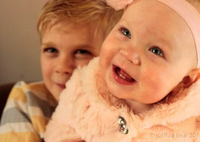 Smiling baby with brother in background