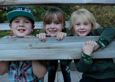 3 kids peaking over a rail
