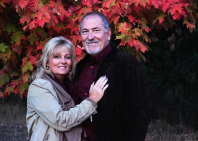 Couple in front of autumn leaves