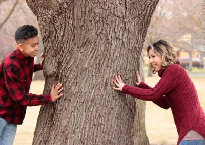 Mother and son looking around a tree