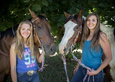 Portrait of mother and daughter with their horses