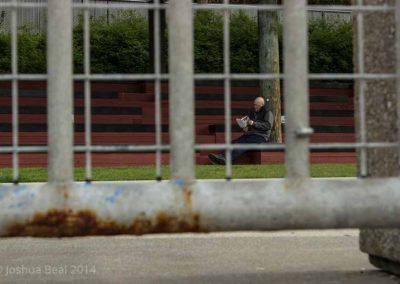 Man reading as seen through a fence