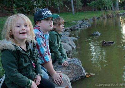 3 kids on rocks at the edge of a pond
