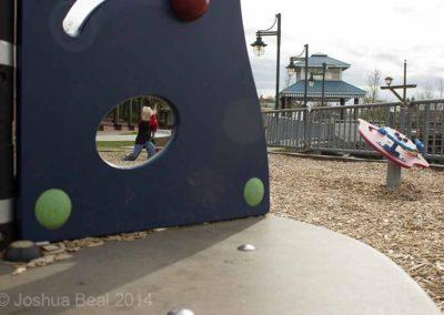 Child seen through playground frame