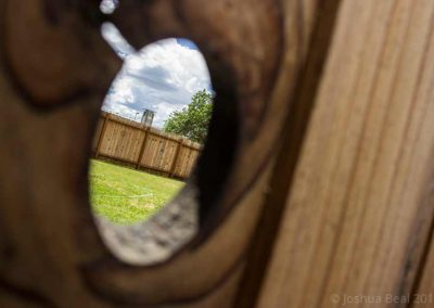 Distant clock tower seen through an empty fence knot